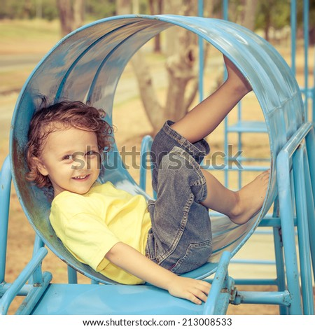 Happy little girl in the playground at the day time - stock photo