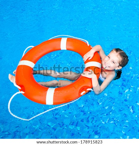 happy little girl in the pool floating on the Lifebuoy - stock photo