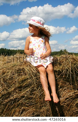 Happy little girl in white sundress and hat on the haystack - stock photo