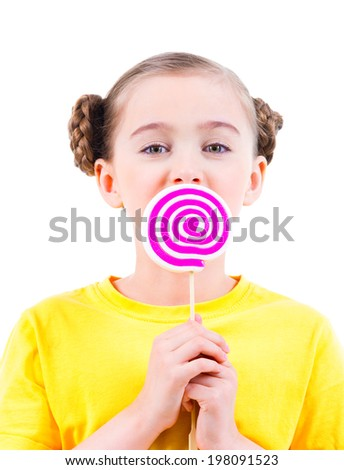 Happy little girl in yellow t-shirt eating colored candy - isolated on white. - stock photo