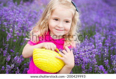 happy little girl is in a lavender field holds a basket of flowers - stock photo