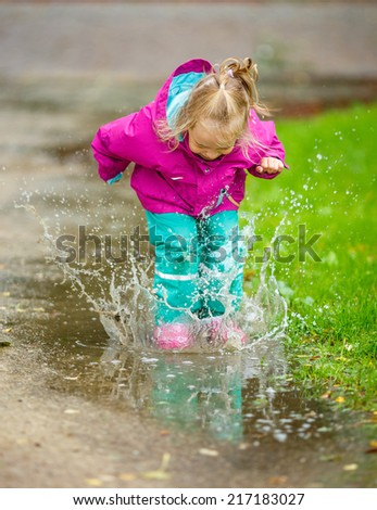 Happy little girl jumps into a puddle - stock photo