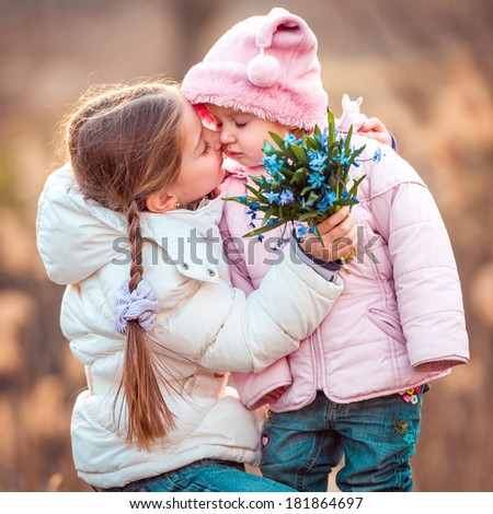 happy little girl kissing her sister and holding a bouquet of snowdrops - stock photo