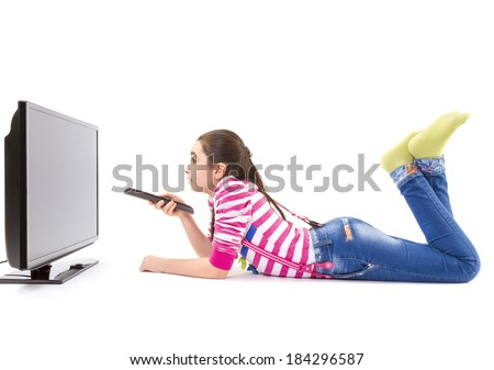 Happy little girl laying down and watching tv - stock photo