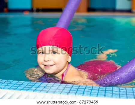 Happy little girl learning to swim with pool noodle - stock photo