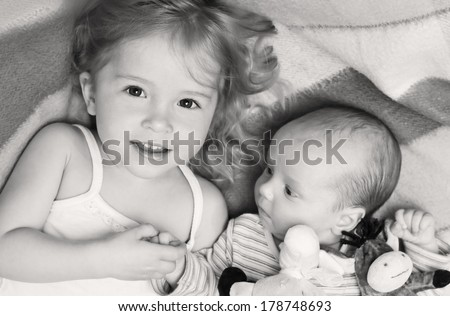 happy little girl lovingly holding the hand of a newborn brother ( black and white ) - stock photo