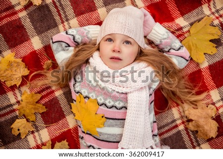 Happy little girl lying on a blanket while walking in the autumn park. top view - stock photo