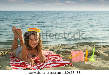 happy little girl lying on beach  - stock photo