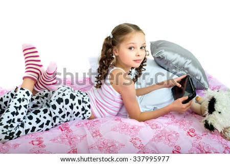 Happy little girl lying on bed with tablet computer. Kid and handheld internet electronic device. Child and gadgets. - stock photo