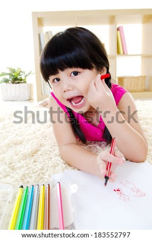 Happy little girl lying on the floor and colouring - stock photo