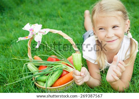 Happy little girl lying on the grass with a basket of vegetables at the day time. Concept of healthy food. - stock photo