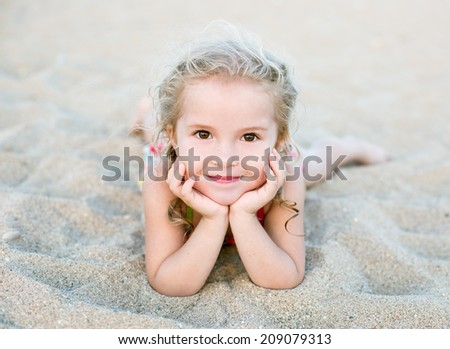 Happy little girl lying on the sand on the beach - stock photo