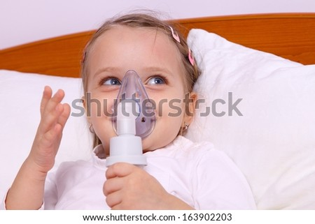 Happy little girl making aerosol treatment in bad - stock photo