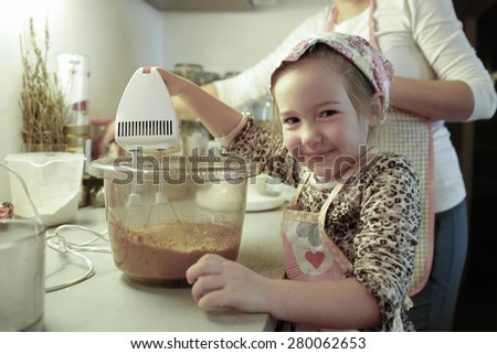 Happy little girl mixing dough for a birthday cake, being independent and proud, helping mum in the kitchen. Independence, family values, inclusion, learning through experience concept.  - stock photo