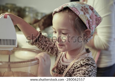 Happy little girl mixing dough for a birthday cake, being independent, helping mum in the kitchen. Independence, family values, inclusion, learning through experience concept.  - stock photo