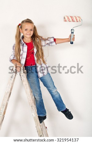 Happy little girl on a ladder with roller brush - having fun repainting the room - stock photo