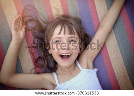 happy little girl on a rainbow hammock - stock photo