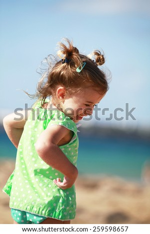 Happy little girl on beach - stock photo