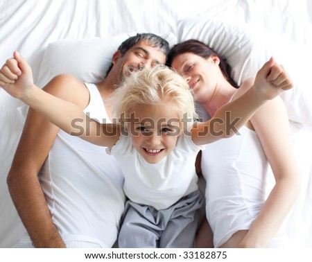 Happy little girl on bed with her parents in the morning - stock photo