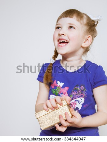 Happy little girl opening a gift box - stock photo