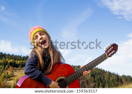 Happy little girl playing a guitar outdoor - stock photo