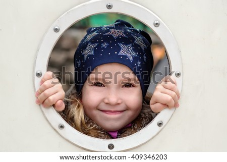 Happy little girl playing hide and seek outdoors - stock photo