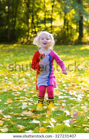 Happy little girl playing in the park on sunny autumn day. Cute funny kid eating big colorful lollipop outdoors. - stock photo
