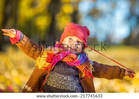 Happy little girl playing in the sunny autumn park - stock photo