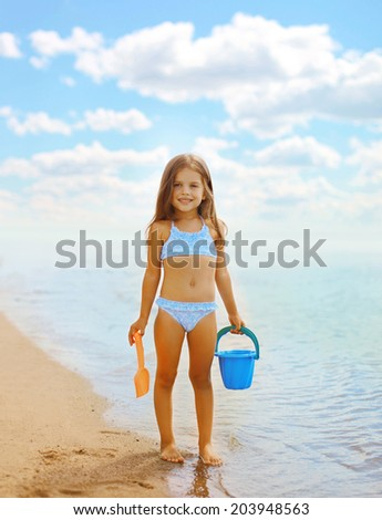 Happy little girl playing on the beach near sea, summer, vacation, family - concept - stock photo