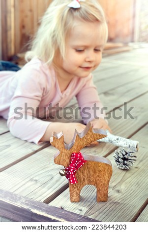 Happy little girl playing with Christmas decorations - reindeer and cones. Natural lighting setting. - stock photo