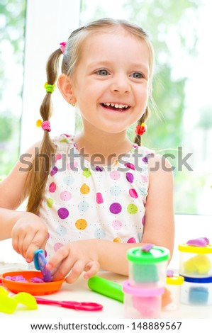 Happy Little Girl Playing with Color Play Dough - stock photo