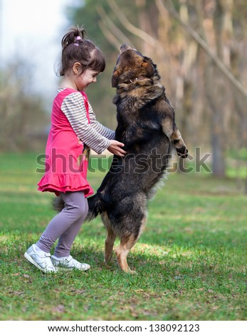 Happy little girl playing with dog - stock photo