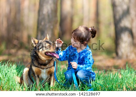 Happy little girl playing with dog on the grass - stock photo