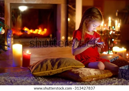 Happy little girl playing with her smart phone by a fireplace in a cozy dark living room on Christmas eve - stock photo