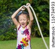 Happy little girl pours water from a hose - stock photo