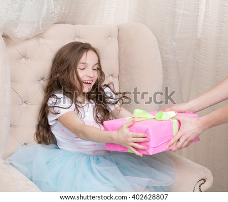 Happy little girl receiving gift box with ribbon and bow - stock photo