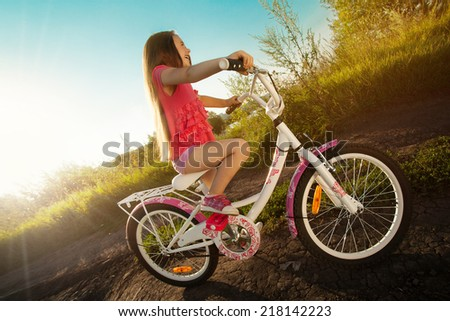 Happy little girl riding a bicycle . Active Leisure Concept. Healthy lifestyle. - stock photo