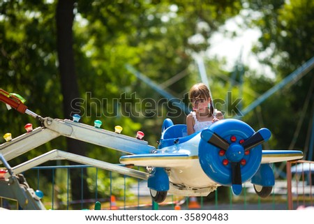 Happy little girl riding carousel in toy airplane - stock photo