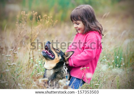 Happy little girl riding her dog on the field - stock photo