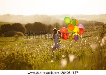 Happy little girl running across the field with balloons - stock photo