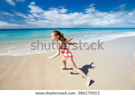 Happy little girl running and splashing at shallow water at beach having a lot of fun on summer vacation - stock photo