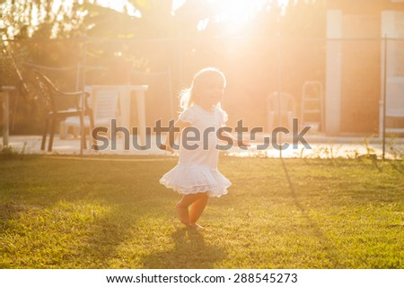 Happy little girl running in the yard - stock photo