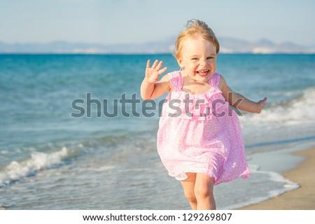 Happy little girl running on the beach - stock photo