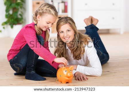 Happy little girl saving her pocket money sitting on the living room floor with her attractive young mother putting coins into the slot of a piggy bank - stock photo