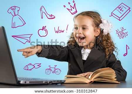 Happy Little Girl Sits At Table With Book Shows A Finger Into The Laptop On Blue Background. Back To School Theme - stock photo