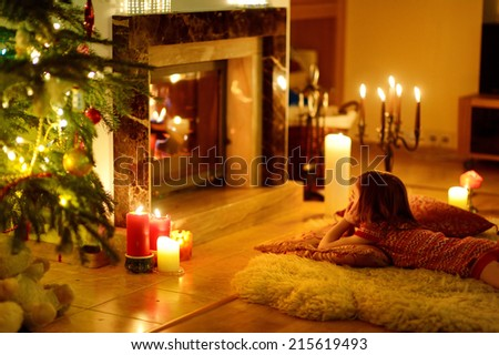 Happy little girl sitting by a fireplace in a cozy dark living room on Christmas eve - stock photo