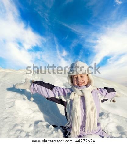 Happy little girl sitting in the snowy field - stock photo