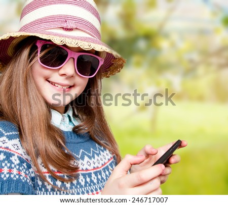 Happy little girl sitting on char in suny day - stock photo