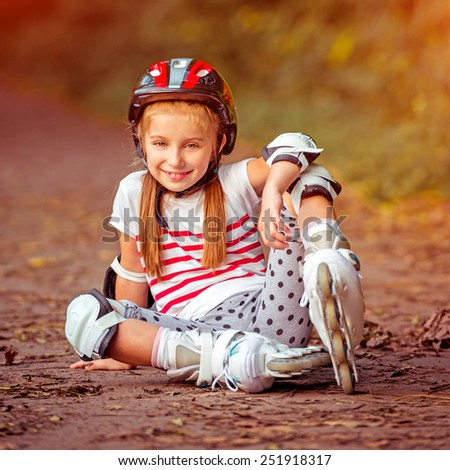 happy little girl sitting on roller skates in the autumn forest - stock photo