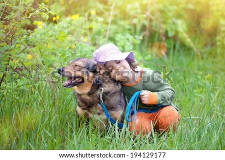 Happy little girl sleeping with dog on the grass - stock photo